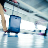 Airport rush. People with their suitcases walking along a corridor (motion blurred image; color toned image Royalty Free Stock Images