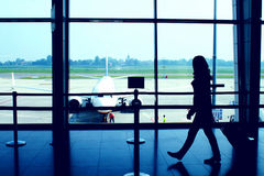 Airport scene. Classic airport scene with woman carrying luggage in the airport departure gate, plane parked at the gate in background stock photo