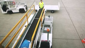 Airport scene with bagagge. HEATHROW, UNITED KINGDOM - June 01, 2014: Airport employees load and unload baggage on conveyor to and from commercial airline jumbo stock video