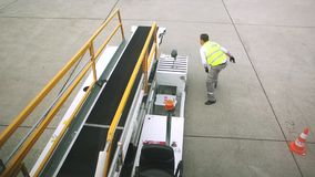 Airport scene with bagagge. HEATHROW, UNITED KINGDOM - June 01, 2014: Airport employees preparing to load and unload baggage on conveyor to and from commercial stock video footage