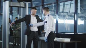 Security agent using a metal detector on a man. Airport security agent using a metal detector on a male passenger in a suit to pat him down at the boarding gate royalty free stock images