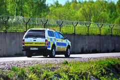 Airport security car is riding along the fence surrounding the runway of Pulkovo International Airport Stock Image