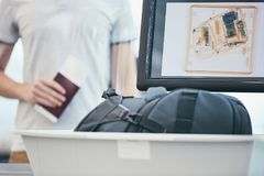 Airport security check. Young man holding passport and waiting for x-ray control his luggage royalty free stock photography