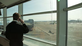Airport Security Officer in uniform watching aerodrome traffic and talking on phone. stock footage