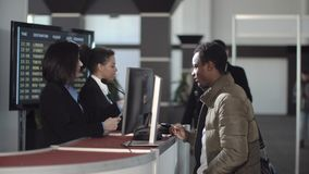 Airport security personnel checking identification. Two female airport security personnel checking identification at a check-in or boarding counter at the Royalty Free Stock Photography