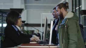Airport security personnel checking identification. Two female airport security personnel checking identification at a check-in or boarding counter at the Stock Image