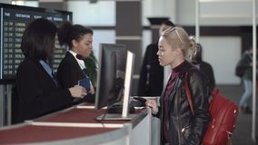 Airport security personnel processing passengers. At a check-in counter in a departures or arrivals hall checking their identity against passports and thumb stock footage