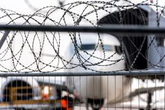 Airport security zone. Blurred aircraft behind a barbed wire fence. Illustration of the incident in aviation transport royalty free stock photo