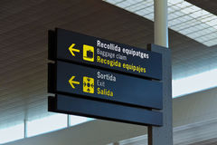 Airport Sign. An airport sign indicating directions to the exit and baggage claim in English, Spanish, and Catalan Stock Image