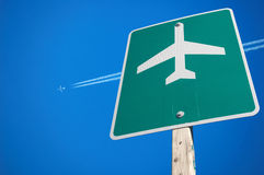Airport sign. Highway sign for an airport with an airplane flying high above Royalty Free Stock Images