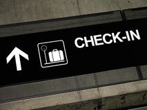Airport signs - Check-in. Airport sign pointing to check-in area, placed on exposed concrete beam Royalty Free Stock Images