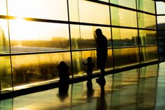 Airport, silhouette of father with kids, blurred aircrafts behind tall windows, Dublin Ireland, sunrise royalty free stock photos