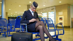 At the airport sits stewardess with luggage and holding smartphone. stock video footage