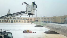 Airport staff performs anti-icing treatment of the aircraft stock footage