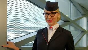 In airport stewardess with blond hair and glasses smiling affably. European woman dressed in dark uniforms with red trim around the edge. Scarlet scarf tied on stock video footage