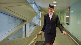 At the airport stewardess with suitcase goes and looks at his watch. At the airport flight attendant with suitcase goes and looks at his watch. High beautiful stock footage