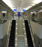 Airport terminal. A typical airport terminal with two escalators and LCD monitors for flight information Stock Photography