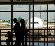 Airport terminal. A family at an airport terminal with aeroplane in the background royalty free stock photos
