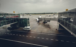 Airport terminal with airliners at boarding gates at rainy day Royalty Free Stock Image