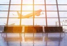 Airport terminal interior design. Airport terminal interior with seats, windows with city view, sunlight and an airplane flying by. 3D Rendering Royalty Free Stock Image