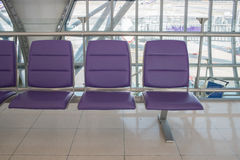 Airport terminal interior with rows of empty seats, city view an Stock Images