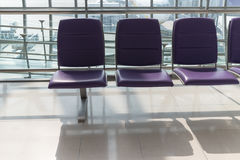 Airport terminal interior with rows of empty seats, city view an Royalty Free Stock Photo