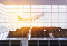 Airport terminal interior with sunlight. Airport terminal interior design with seats, framed windows with city view, sunlight and an airplane flying by. 3D Stock Photo