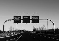 Airport Terminal signs, arrival, departure in Monochrome. Monochrome photograph of road leading up to airport with terminal signs in center of photo. Good for stock photos