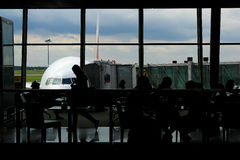 Airport Terminal. Silhouette of passengers at the airport terminal waiting for flight with airpane at the background Stock Photography