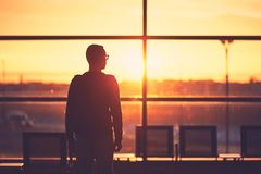 Airport terminal at the sunset. Silhouette of the young man at the airport. Traveler leaves to the gate during golden sunset Stock Image