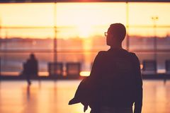 Airport terminal at the sunset. Silhouette of the young man at the airport. Traveler leaves to the gate during golden sunset Royalty Free Stock Images