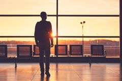 Airport terminal at the sunset. Silhouette of the young man at the airport. Traveler leaves to the gate during golden sunset Royalty Free Stock Image