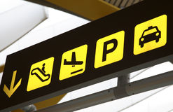 Airport transportation sign. Yellow transportation sign at airport highlighting parking and arrivals of planes Stock Photo