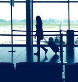 Airport travel. Classic airport scene with woman carrying luggage in the airport departure gate preparing to travel by plane stock photo