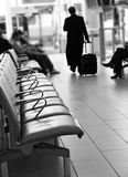 Airport travel lounge & man traveling. Abstract black and white image of travelers in an airport waiting area with seating.  A man walking away leaving Royalty Free Stock Photos