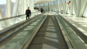 Airport Travelers On Moving Walkway Tilt Shift. V26. Airport travelers walking by while on moving walkway stock video