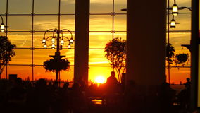 Airport Travelers People Silhouette Sunset. V12. Silhouette clip of airport travelers walking by and sitting at tables with sunset background stock video footage