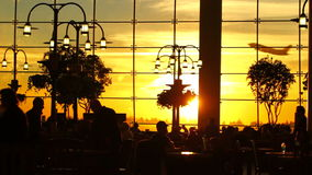 Airport Travelers People Silhouette Sunset. V7. Silhouette clip of airport travelers walking by and sitting at tables with sunset background and airplane taking stock footage