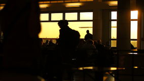 Airport Travelers People Silhouette Sunset. V5. Silhouette clip of airport travelers walking by, waiting in line, and sitting in seats stock video footage
