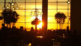 Airport Travelers Sequence People Silhouette Sunset. V13. A sequence of silhouette clips of airport travelers walking by and sitting at tables with sunset stock footage