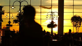 Airport Travelers Sequence People Silhouette Sunset. V8. A sequence of silhouette clips of airport travelers walking by and sitting at tables with sunset stock footage
