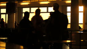 Airport Travelers Sequence People Silhouette Sunset. V3. A sequence of silhouette clips of airport travelers walking by, waiting in line, and sitting in seats stock video