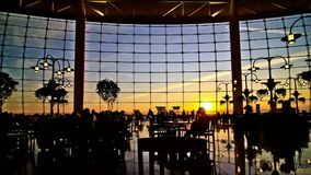 Airport Travelers Time Lapse People Silhouette Sunset. V8. Silhouette time lapse clip of airport travelers walking by and sitting at tables with sunset stock video footage