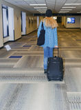 Airport, traveling. Woman at the airport carrying luggage stock photo