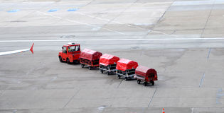 Airport trucks handling baggage Stock Image