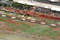 Airport Under Construction. Aerial view of Hawaiian airport under going construction, showing landing strip, red dirt with heavy equipment, helicopter on landing Royalty Free Stock Image