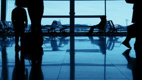 Airport. Unrecognizable Silhouettes of Passengers. Airport. The waiting room. Passengers with a child are boarding. Unrecognizable silhouettes stock video footage