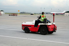 Airport vehicle. Airport worker on a vehicle, racing down the runway Stock Photo