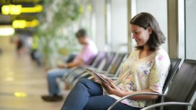 Airport Waiting Area. Beautiful young woman using a digital tablet in airport waiting area stock video footage