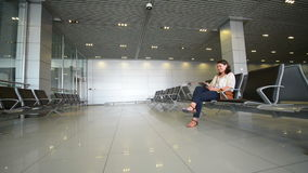 Airport Waiting Area. Young woman using a digital tablet in airport waiting area stock video footage